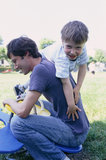 Father and son playing on seesaw
