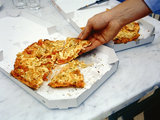 Man's hand taking a piece of pizza