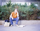 Man sitting on pavement with bag, city map and bottle of water
