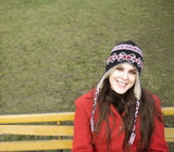 Young woman wearing hat sitting on bench, smiling, portrait