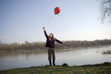 Girl (10-12) standing by river holding red balloon, looking upwards
