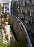 Woman sunbathing on city balcony