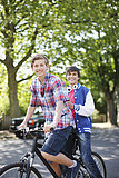 Smiling teenage boys riding bicycle together