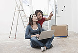 Germany, Cologne, Young couple using laptop and pointing in renovating apartment