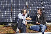 Germany, Munich, Two man sitting and talking in solar plant