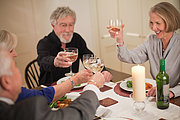 Senior friends raising glasses at dinner party
