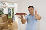Germany, Bavaria, Grobenzell, Mature man holding model house near cardboard box, smiling, portrait