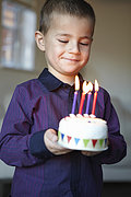 Boy holding miniature cake with candles