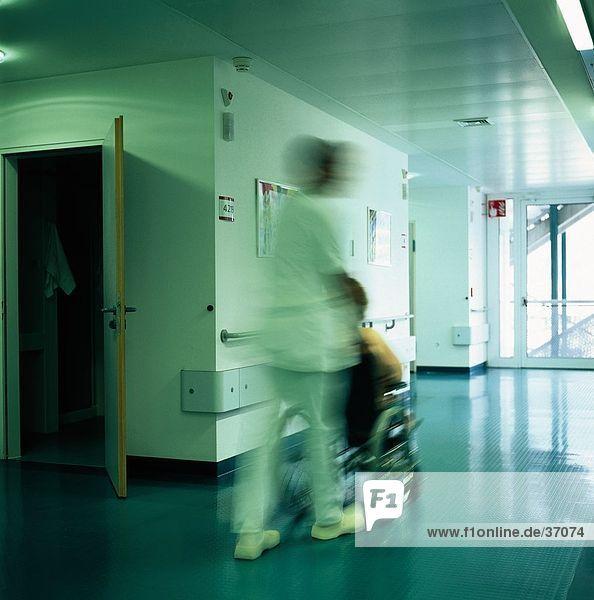Druck ein Patienten im Rollstuhl in einem Krankenhaus Krankenschwester