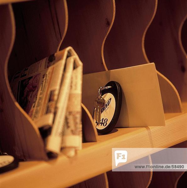 Nahaufnahme der gefalteten Zeitung und Schlüssel auf Regal