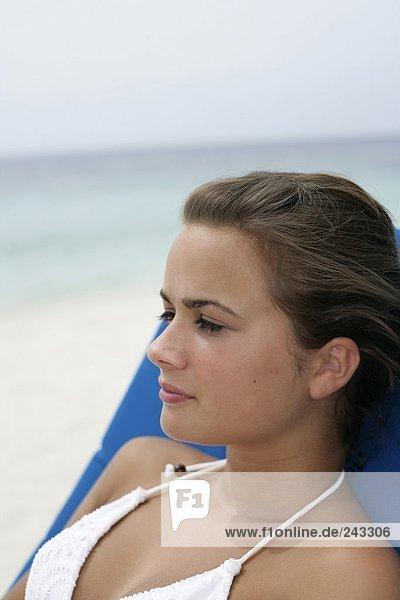 junges m dchen im bikini sitzt auf sonnenliege am strand fully released lizenzfreies bild. Black Bedroom Furniture Sets. Home Design Ideas