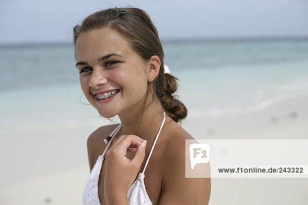 Junges Mädchen am Strand lacht in Kamera, trägt Zahnspange