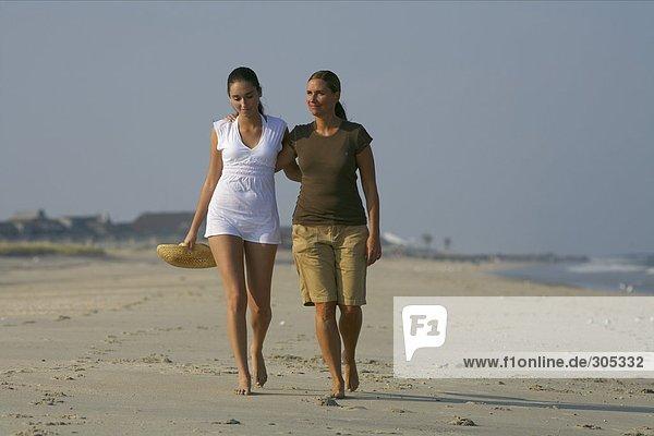 Zwei junge Frauen gehen am Strand spazieren - Freundinnen