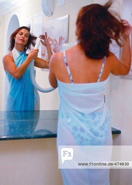 Reflexion der junge Frau trocknen Haare in einem Spiegel