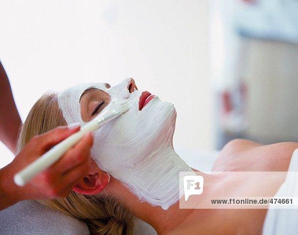 Weibliche Therapeut Gesichtscreme auf junge Frau Gesicht Umsetzung