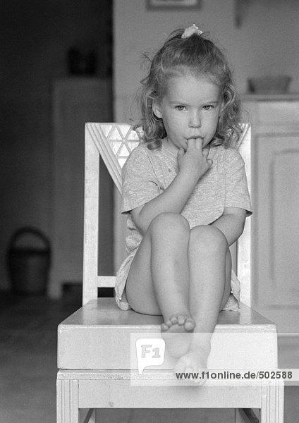 Kleines Mädchen sitzen mit Fingern in Mund, b&w