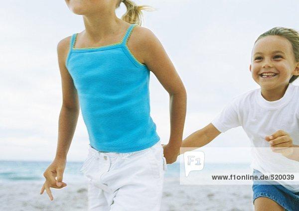 Zwei kleine Mädchen, Hand in Hand am Strand - Lizenzfreies