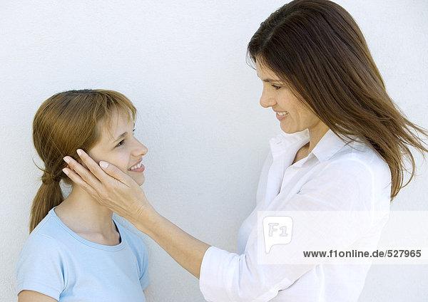 Mutter ihre Tochter, lächelnd und streicheln Wange