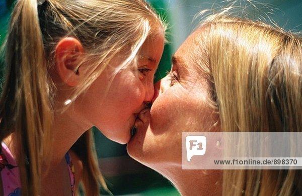 Mutter und Tochter küssen - Lizenzpflichtiges Bild