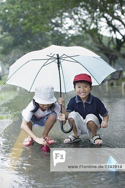 Zwei junge Kinder im Freien im Regen spielen mit Papier Boote