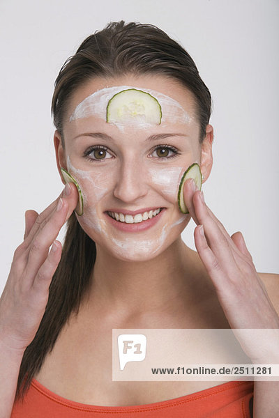 Young woman applying a cucumber face mask - Royalty Free Image - F1online Stock Photo Agency 2511281