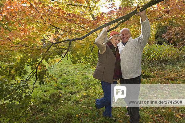 Porträt von Paar hält Zweig in Wäldern