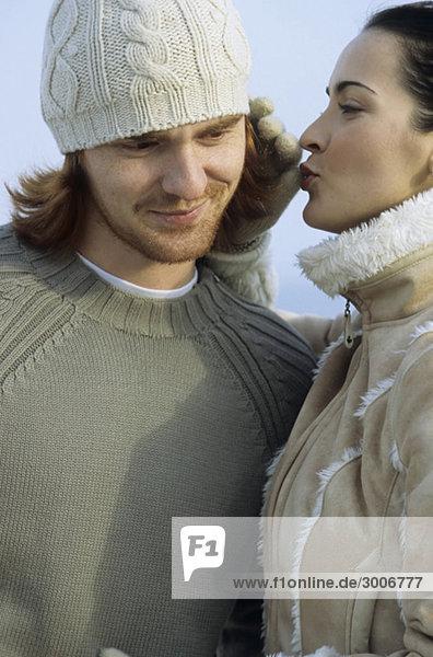 Junge brünette Frau pustet ihrem Freund ins Ohr - Liebkosung - Beziehung - Winter