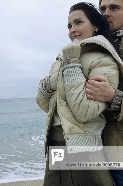 Rothaariger Mann hält eine junge brünette Frau in seinen Armen - Liebe - Zweisamkeit - Strand - Winterbekleidung