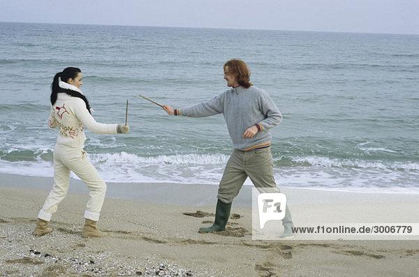 Junges Paar kämpft mit kleinen Stöcken - Schwertkampf-Imitation - Spaß - Freizeit - Strand