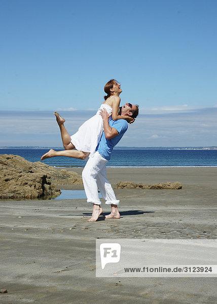 Mann hebt Frau am Strand hoch, Seitenansicht