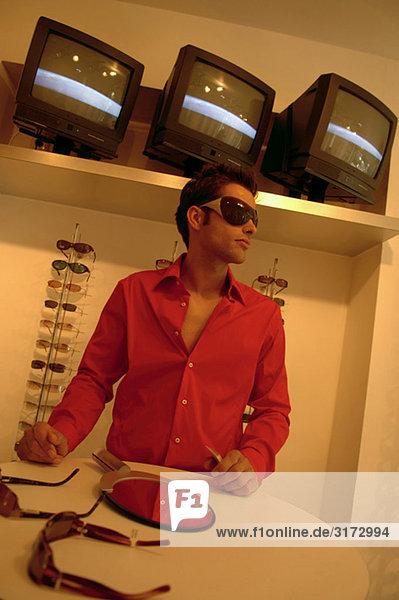 Junger dunkelhaariger Mann in einem Geschäft für Sonnenbrillen - Einkaufen