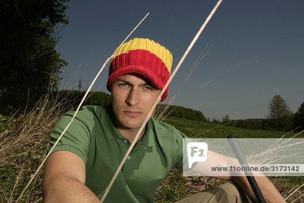 Junger Mann mit Wollmütze auf Golfplatz