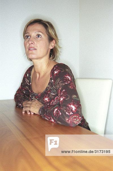 Blonde Frau sitzt an Tisch