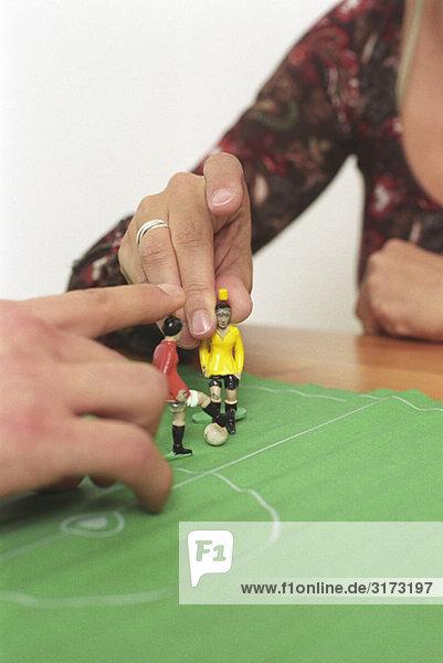 Menschen spielen mit Tischfussballspiel (Detail)