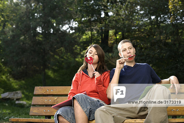 Teenagerpaar sitzt auf einer Parkbank und isst Lutscher