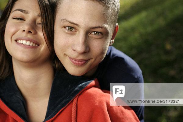 Teenagerpaar umarmt sich und blickt in die Kamera