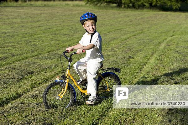 kind kleiner junge 4 jahre mit fahrrad und helm auf. Black Bedroom Furniture Sets. Home Design Ideas