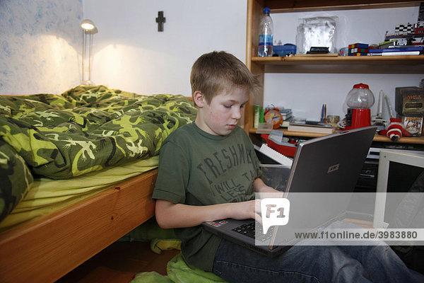 junge 11 jahre alt arbeitet mit seinem computer zuhause in seinem kinderzimmer macht. Black Bedroom Furniture Sets. Home Design Ideas