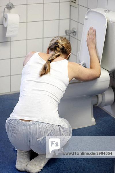 Junge Frau übergibt sich in eine Toilette, Unwohlsein