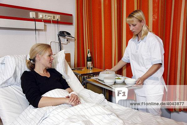 krankenschwester bringt einer patientin das essen ans bett im krankenhaus lizenzpflichtiges. Black Bedroom Furniture Sets. Home Design Ideas