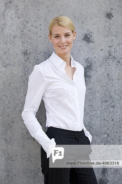 junge blonde frau im business look steht vor einer grauen wand lizenzpflichtiges bild. Black Bedroom Furniture Sets. Home Design Ideas