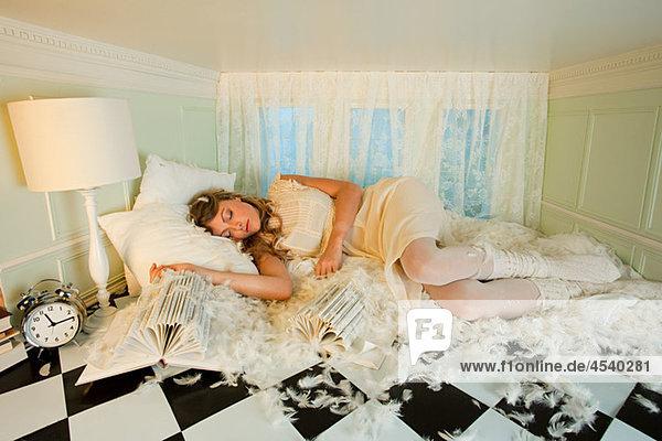 Junge Frau unter Kissen Federn in kleinen Raum schlafen