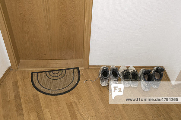 schmutzige schuhe im hausflur neben der wohnungst r eines mehrfamilienhauses lizenzpflichtiges. Black Bedroom Furniture Sets. Home Design Ideas