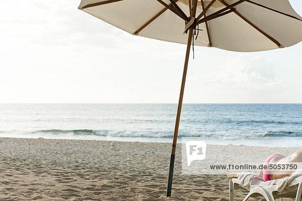 sonnenschirm am strand halbnackte person auf liegestuhl liegen lizenzfreies bild. Black Bedroom Furniture Sets. Home Design Ideas