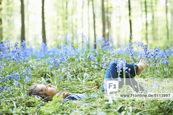 Girl laying in field of flowers - Royalty Free Image ...