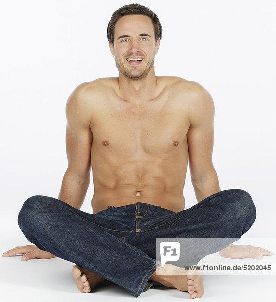 Mann in Jeans, Nackter Oberkörper, Schneidersitz