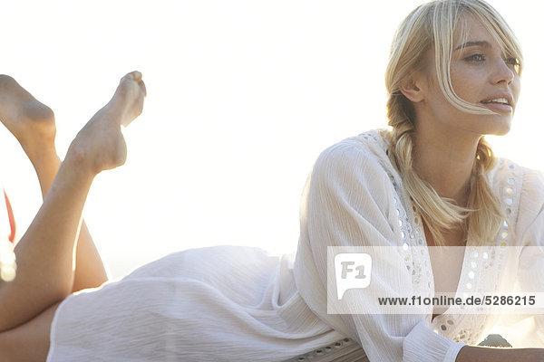 Blonde Mädchen in Zöpfen auf Bauch liegend