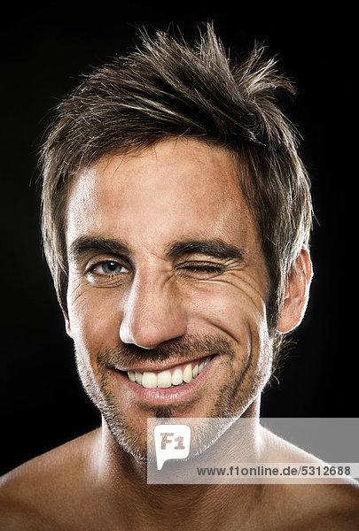 Lächelnder junger Mann mit Augenzwinkern, Portrait