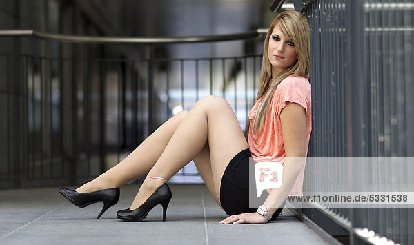 Lastest  Haired Cheerful Girl In A Short Skirt Sitting On A Chair And Gesturing