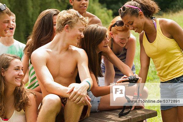 Jugendliche Fotos zusammen auf ein Freund der Kamera überprüfen